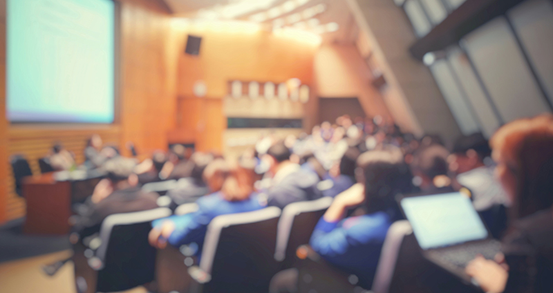 blurry image of people seated in a large lecture hall